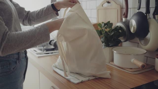 giovane donna che torna a casa dal viaggio dello shopping spacchettando sacchetti di plastica gratuiti per la spesa - grocery home video stock e b–roll