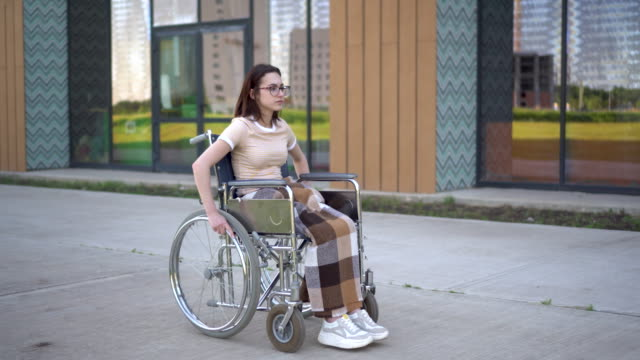 A young woman rides a wheelchair and a heart attack occurs. A girl in a wheelchair against the background of a glass building grabs her heart. Special transport for the disabled.