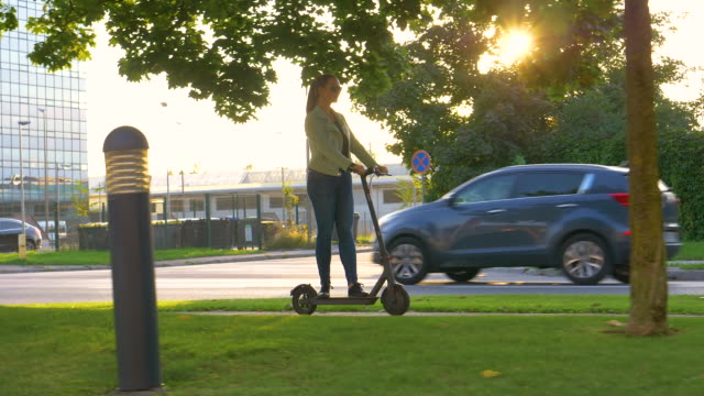 slow motion: young woman rides an e-scooter along a sidewalk in the modern city - monopattino elettrico video stock e b–roll