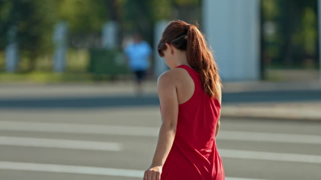 young woman rides on roller skates, balances with her hands. woman moves her body, turns her shoulders. view from the back. 4k, 10bit, prores - łyżwa filmów i materiałów b-roll