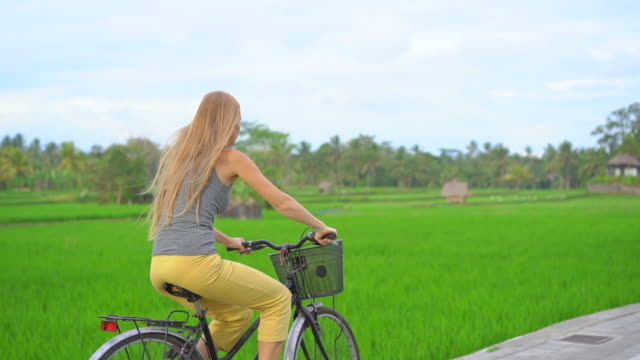 A young woman rides through the beautiful rice field on a bicycle. Travel to South-East Asia concept. Slow motion shot