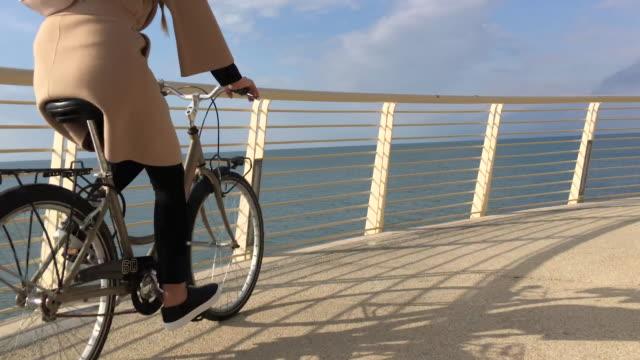 Joven mujer montando una bicicleta - vídeo