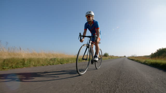 a young woman riding a road bicycle in slow motion. - ciclismo su strada video stock e b–roll
