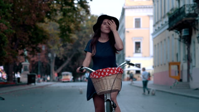 young woman riding an old vintage bike at city center - cestino della bicicletta video stock e b–roll