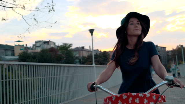 young woman riding on old vintage bike at city center, on the bridge - cestino della bicicletta video stock e b–roll