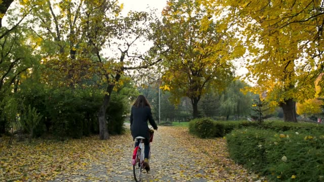 Young woman riding retro bike in empty public park in morning