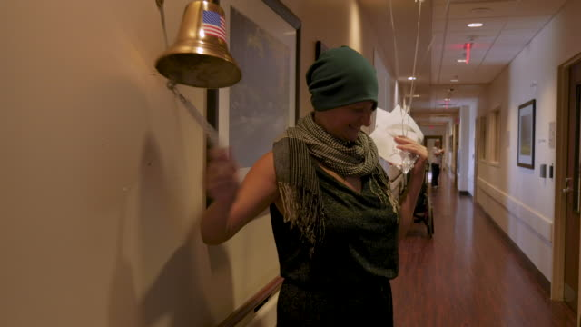 Young woman ringing a bell for finishing her last chemotherapy treatment Young woman ringing a bell for finishing her last chemotherapy treatment for cancer and celebrating her success and remission oncology stock videos & royalty-free footage