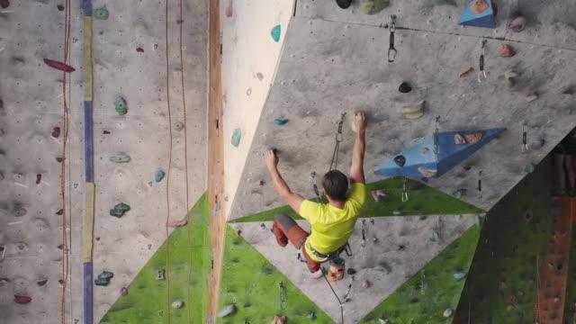junge frau kletterer in klettern at inside kletter-gym. schlanke hübsche frau training an indoor climbing gym wand. - bouldering stock-videos und b-roll-filmmaterial