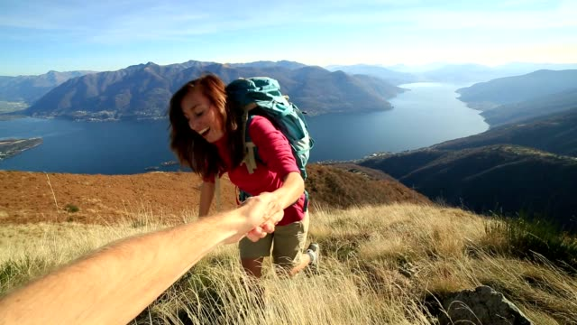 Young woman rock climbing, partner giving helping hand video