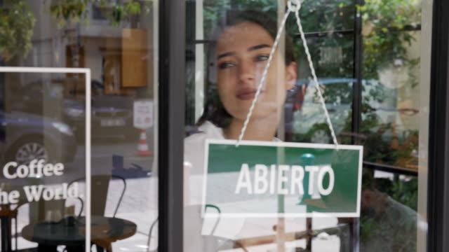 junge frau läuft ein spanisches kleinunternehmen - spanisch stock-videos und b-roll-filmmaterial