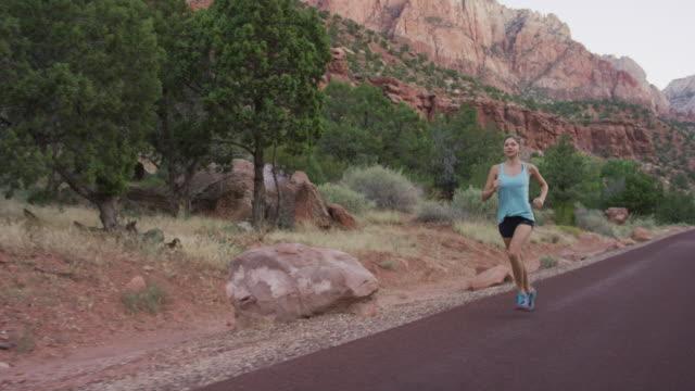 vídeos de stock e filmes b-roll de young woman running along road through canyons - vale