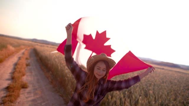 vídeos y material grabado en eventos de stock de joven corriendo y agitando la bandera canadiense en campos - canadá