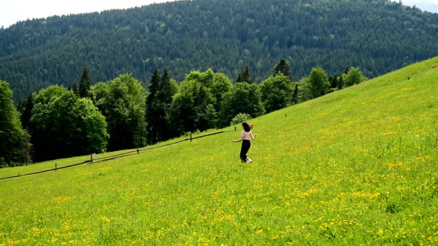 Young woman running down a green mountain meadow. Clear summer day.  Slow motion