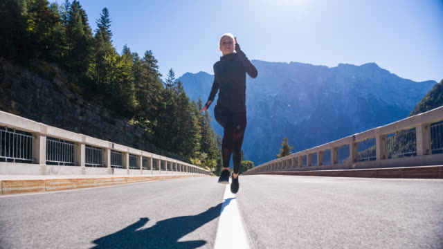 Young woman running in the middle of road toward camera video