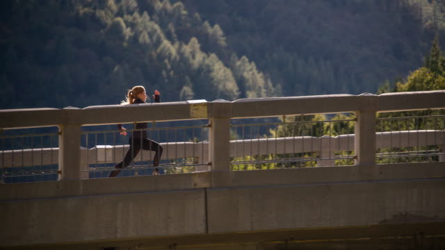 Young woman running on a bridge video