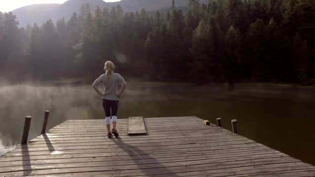 Young woman running on lake pier, rests, Switzerland video