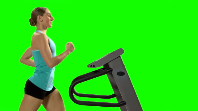 Young woman running on the treadmill. Green screen. video