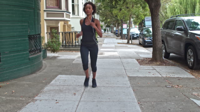 vídeos de stock e filmes b-roll de young woman running outdoors in san francisco - young woman running city