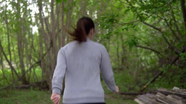 vidéos et rushes de jeune femme en cours d'exécution à travers les bois, regardant en arrière - joggeuse