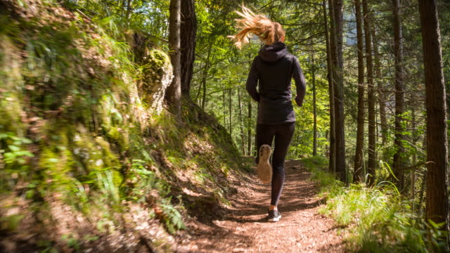 young woman running through the woods - trekking video stock e b–roll
