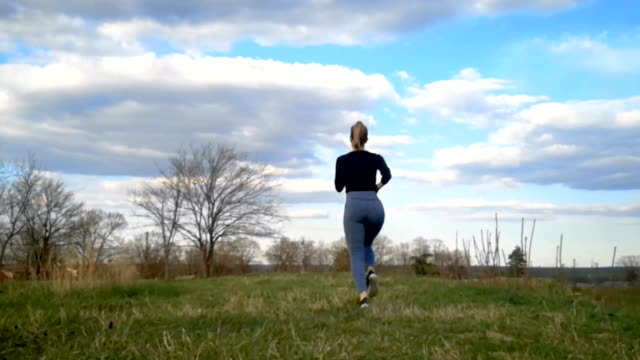 Bидео Young woman running up a grass covered hill. Slow Motion running, Jogging slow motion, beautiful clouds, Athletic Woman Working Out outdoor