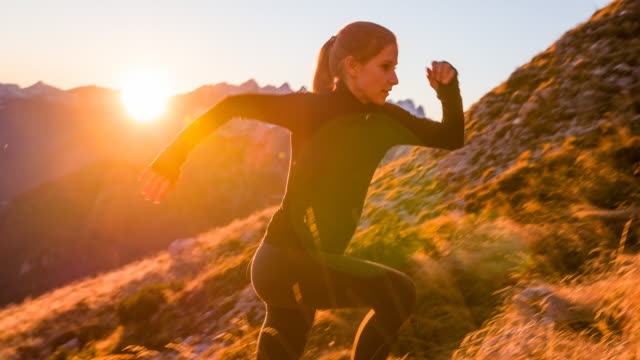 Young woman running up the mountain at sunset Young woman running up the mountain while the sun is slowly setting. recreational pursuit stock videos & royalty-free footage