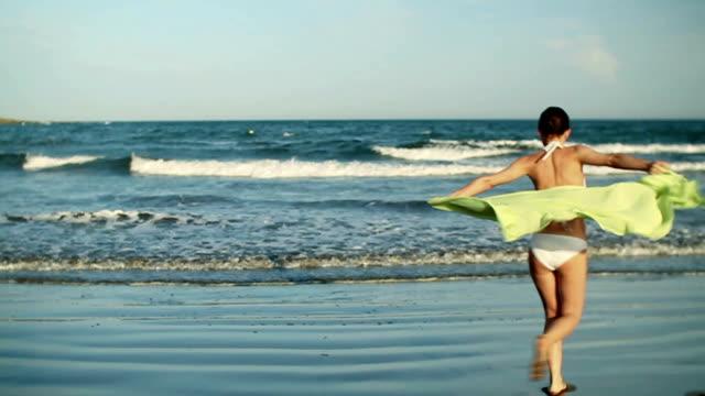 young woman running with sarong at the beach, slow motion - sarong bildbanksvideor och videomaterial från bakom kulisserna