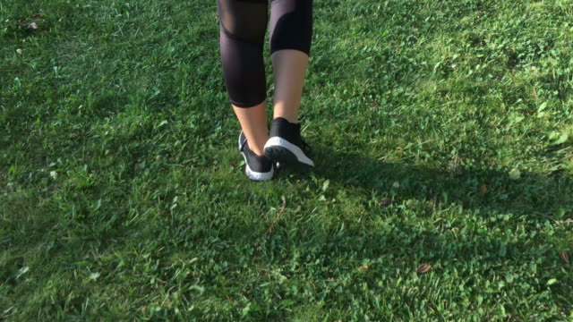 Young Woman Running/Walking at Public Park Young Woman Running at Running/Walking at Public Park. Sports wear. Outdoors. Caucasian. One woman. foot stock videos & royalty-free footage