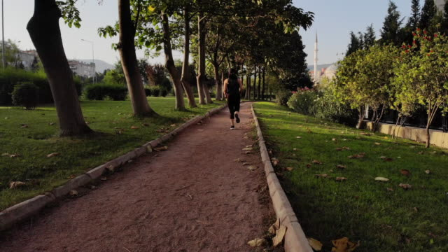 young woman running/walking at public park - 30 34 anni video stock e b–roll