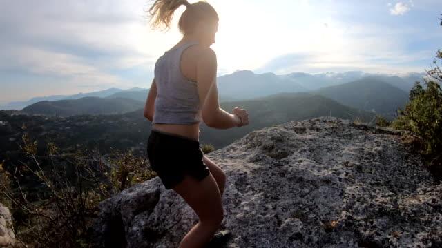 산길을 따라 달리는 젊은 여성 - mountain top 스톡 비디오 및 b-롤 화면