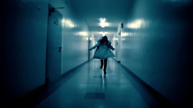 a young woman runs away from her pursuer along a dark corridor - побег стоковые видео и кадры b-roll