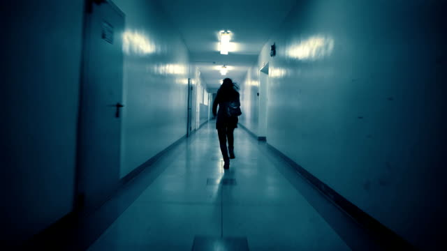 A young woman runs away from her pursuer along a dark corridor