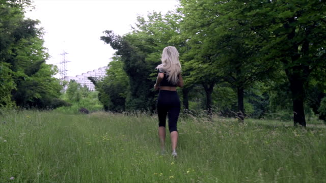 Young woman runs in summer park. video