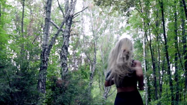 ung kvinna körs i sommaren park. - korsform bildbanksvideor och videomaterial från bakom kulisserna