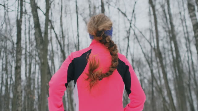 A young woman runs through the park in the winter in a pink jacket. View from the back