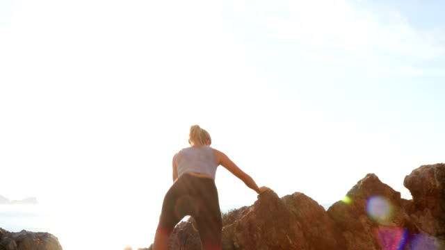 young woman runs up rugged rocks at sunrise - pantaloni capri video stock e b–roll