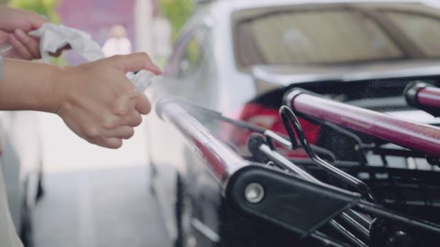 giovane donna che igienò il carrello della spesa al centro commerciale. - grocery home video stock e b–roll