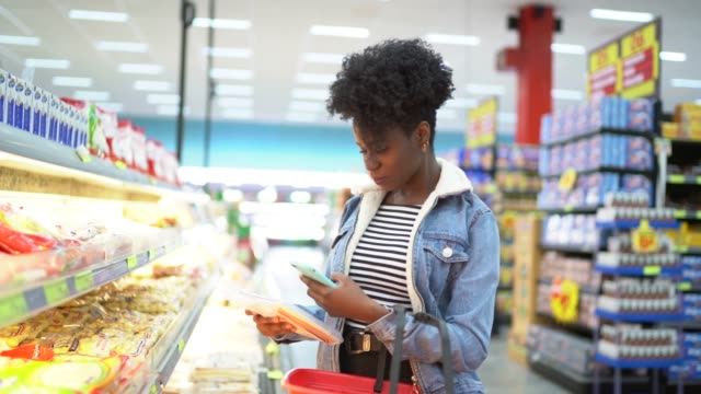 young woman scanning tag of products in supermarket - icona supermercato video stock e b–roll