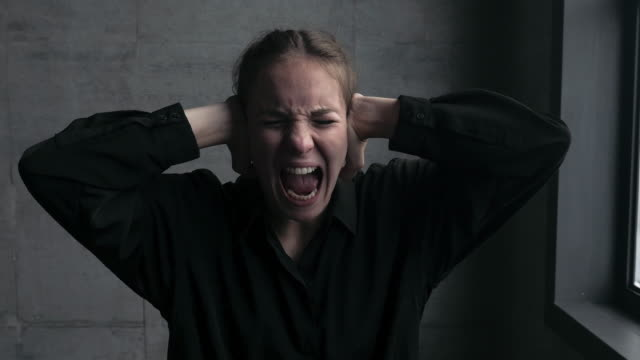 Young Woman Screaming and Tapping Ears