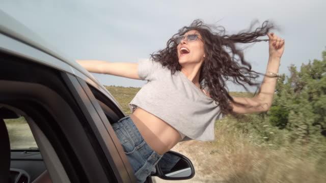 vídeos de stock e filmes b-roll de young woman screaming out of car's window - braços no ar