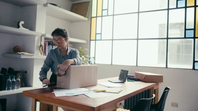 Young woman sealing and sending a package at office