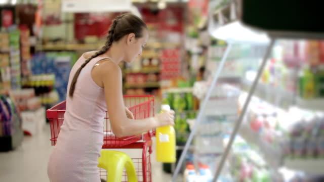 vídeos y material grabado en eventos de stock de joven selección jugo en el supermercado en la sección de refrigerados - zumo