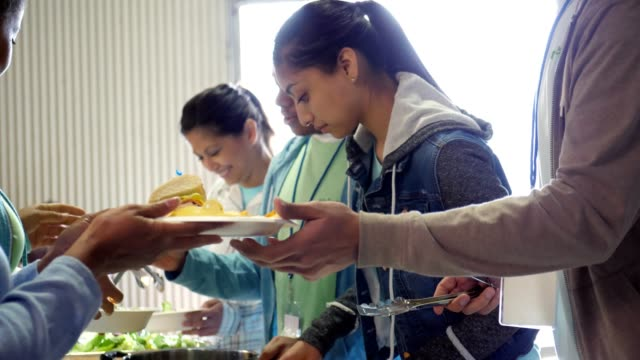 Young woman serves community in soup kitchen Young Hispanic woman volunteering in soup talks with women in the food line. A male volunteer hands a woman a plate of food. The young Hispanic woman smiles while talking with the people receiving a meal. sociology stock videos & royalty-free footage