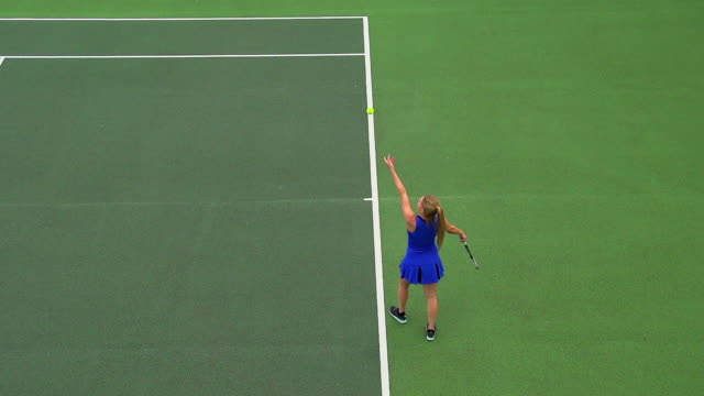 A young woman serves in a tennis match. video