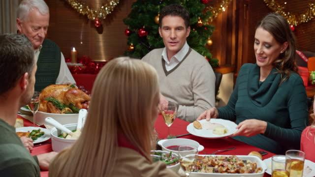 vidéos et rushes de jeune femme avec de la purée de pommes de terre aux autres membres de la famille - diner entre amis