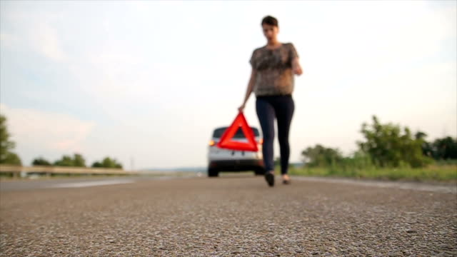 vídeos de stock e filmes b-roll de young woman set warning triangle in the traffic - berma da estrada