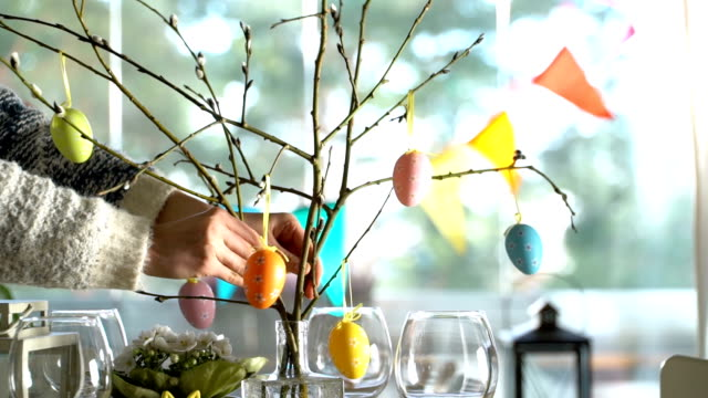young woman setting easter festive table with bunny and eggs decoration - pasqua video stock e b–roll