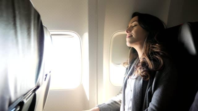 genç kadın uzun bir uçuş sırasında uyku için yerleşir - kulak i̇çi kulaklık stok videoları ve detay görüntü çekimi