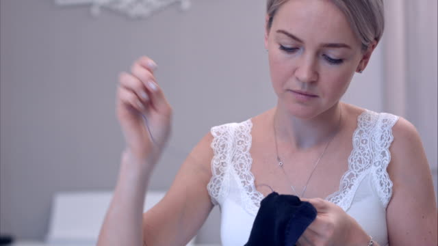 Young woman sewing clothes with a needle video