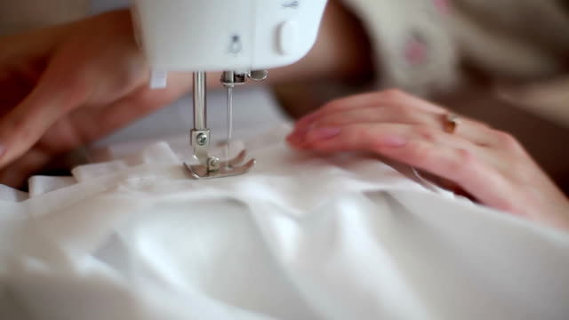 Young woman sewing on the sewing machine. video